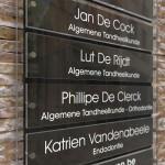 Zwart naambord met huisnummer en 5 losse naamplaatjes.